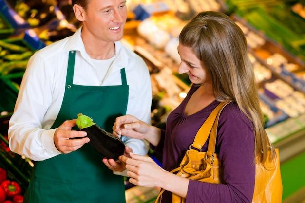 Mulher em um supermercado na prateleira vegetal compras para compras