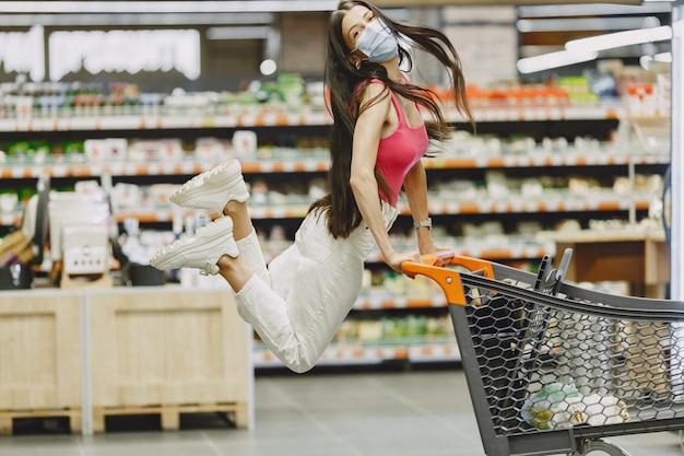 Mulher em um supermercado. senhora em um respirador. a garota faz compras.
