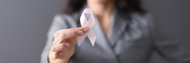 Mulher em um terno cinza segurando uma fita rosa nas mãos, closeup, prevenção do câncer de mama