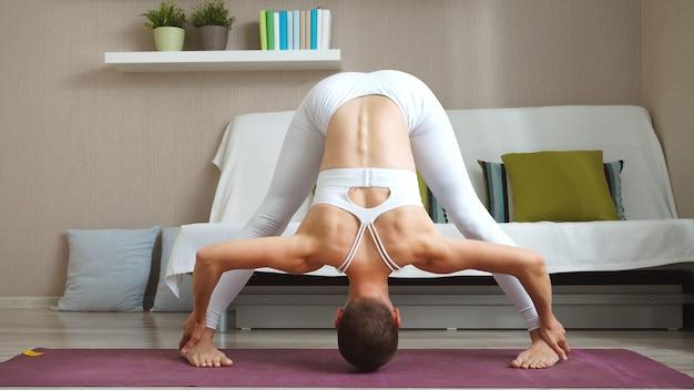 Mulher em um terno de fitness branco está fazendo yoga sentado na sala de estar. auto-isolamento e esportes em casa
