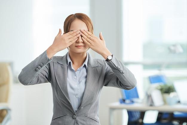 Mulher em um terno de negócio em pé no escritório com as mãos cobrindo os olhos