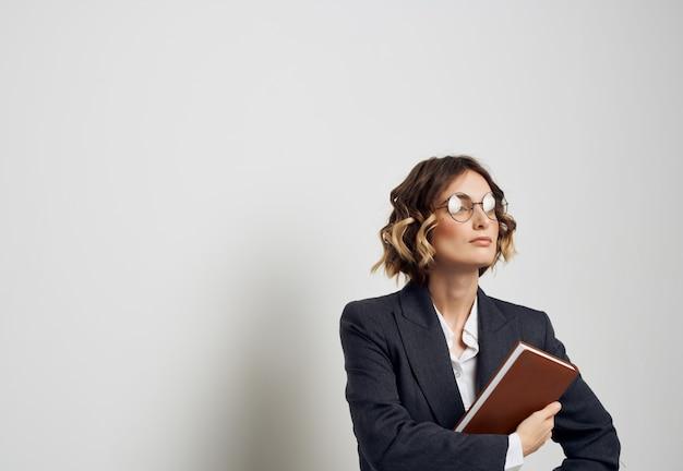 Mulher em um terno de negócio, um caderno na mão, luz de fundo