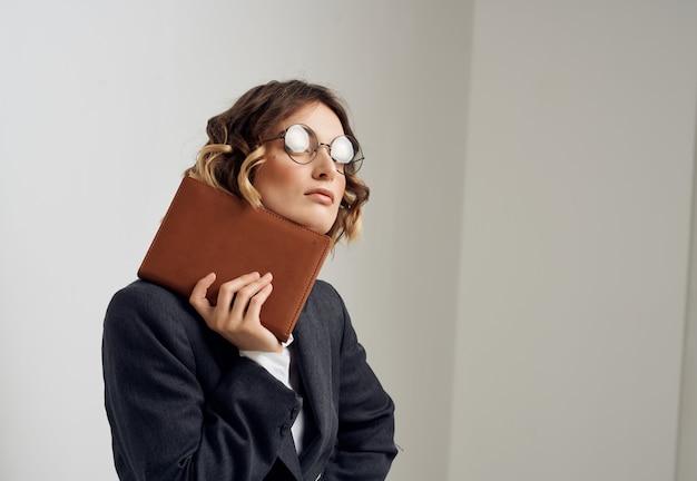 Mulher em um terno de negócios com documentos em mãos, escritório executivo