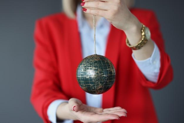 Mulher em um terno de negócios segura a bola com o conceito de diplomacia e política mundial de mapa-múndi