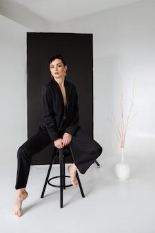 Mulher em um terno masculino no minimalismo de estúdio