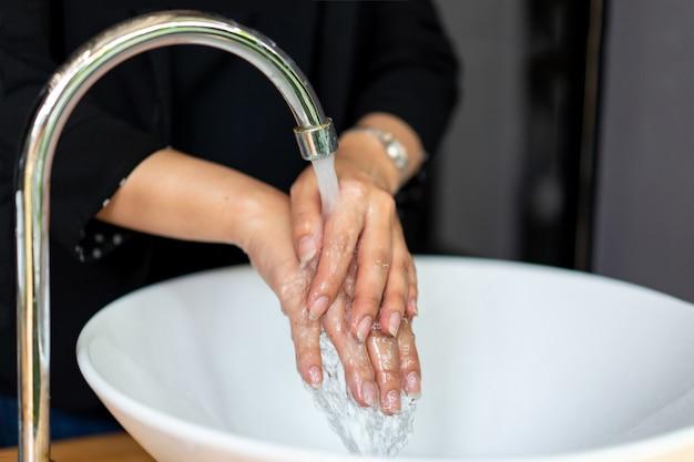 Mulher em um terno preto escuro está lavando a mão na pia.