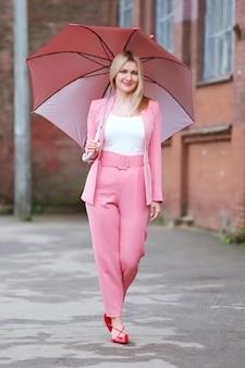 Mulher em um terno rosa com guarda-chuva andando na rua depois da chuva