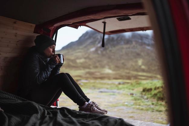 Mulher em um trailer tomando café
