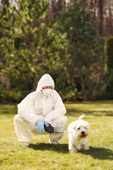 Mulher em um traje de proteção andando com um cachorro