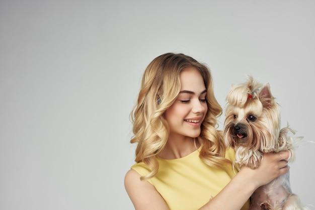 Mulher em um vestido amarelo divertido um pequeno cachorro isolado fundo