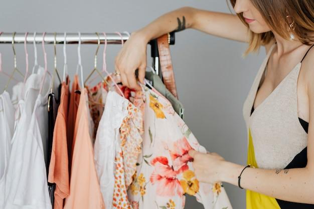 Mulher em um vestido amarelo organizando um vestido em um cabideiro