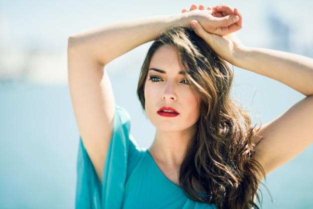 Mulher em um vestido azul com os braços levantados