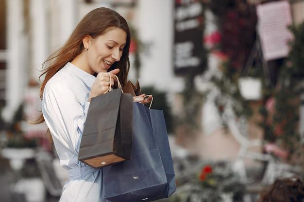 Mulher em um vestido azul com sacola de compras em uma cidade