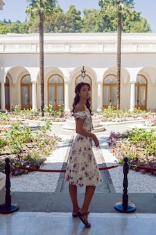 Mulher em um vestido branco com flores parada na entrada da porta do castelo com colunas