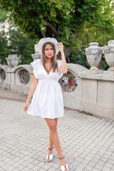 Mulher em um vestido branco e um chapéu branco