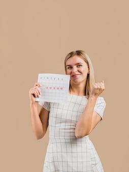 Mulher em um vestido branco, mostrando seu calendário de menstruação