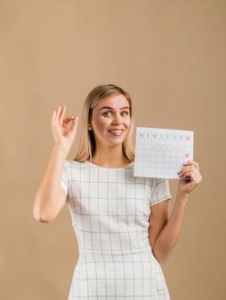 Mulher em um vestido branco, mostrando seu calendário de período