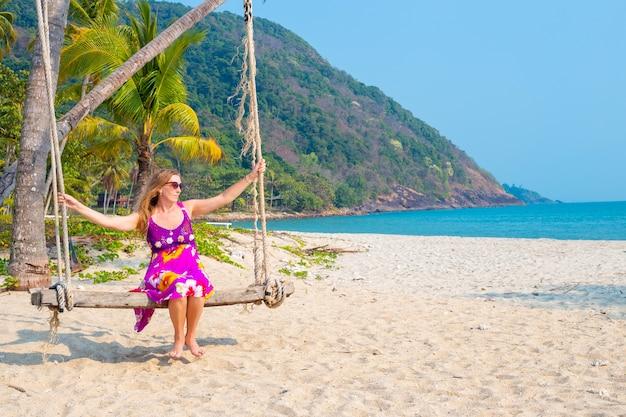 Mulher em um vestido brilhante, balançando em um balanço à beira-mar.