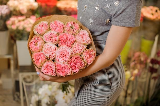 Mulher em um vestido cinza, segurando um buquê de flores cor de rosa