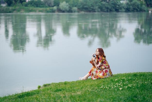 Mulher em um vestido com uma câmera nas mãos na margem do lago