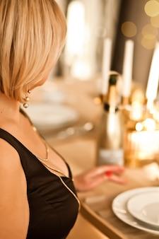Mulher em um vestido de noite com uma taça de espumante champanhe sentado na mesa
