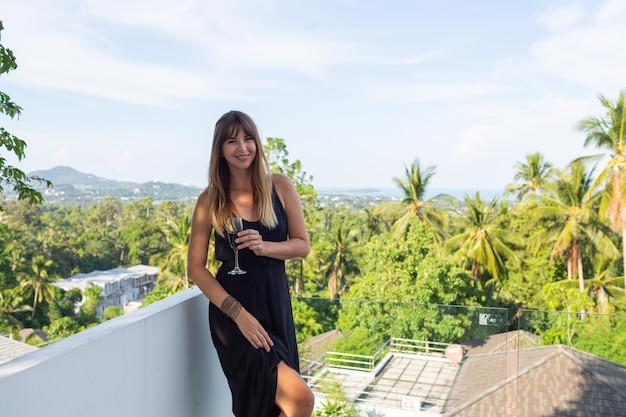 Mulher em um vestido de noite preto com uma taça de vinho na varanda tropical