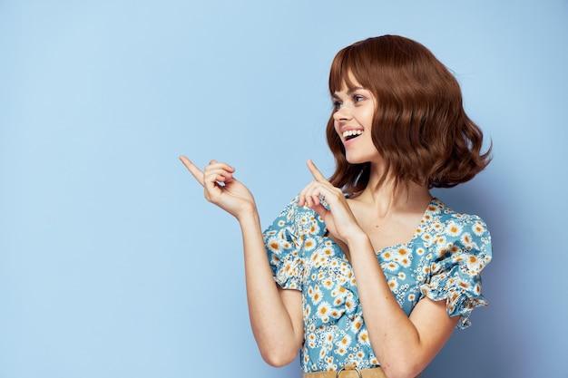 Mulher em um vestido elegante gesto de sorriso com os dedos fundo azul espaço para texto