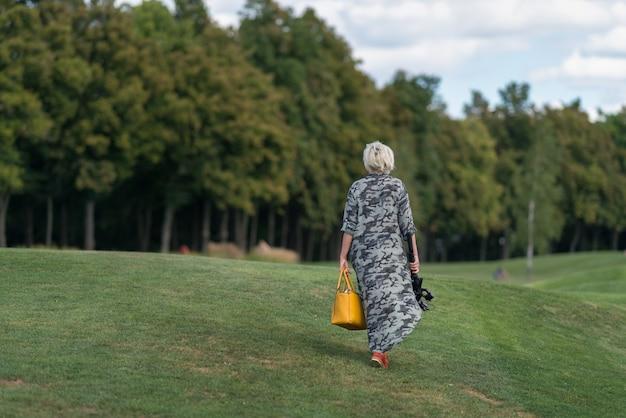 Mulher em um vestido longo carregando uma bolsa e uma câmera em um tripé caminhando sobre a grama bem cortada em um aterro em direção às árvores da floresta em uma visão traseira