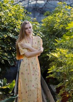 Mulher em um vestido longo de verão posando em uma estufa
