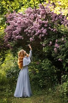 Mulher em um vestido longo lilás no jardim no verão