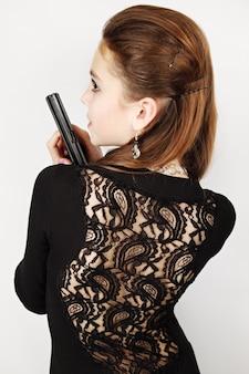 Mulher em um vestido preto com arma