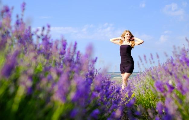 Mulher em um vestido preto de pé em um campo de lavanda de florescência