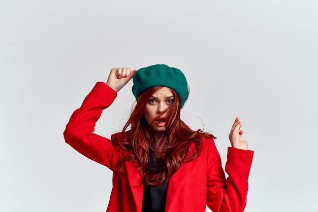 Mulher em um vestido preto e casaco vermelho posando