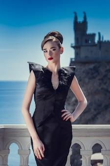 Mulher em um vestido preto longo sobre um fundo de um antigo castelo.