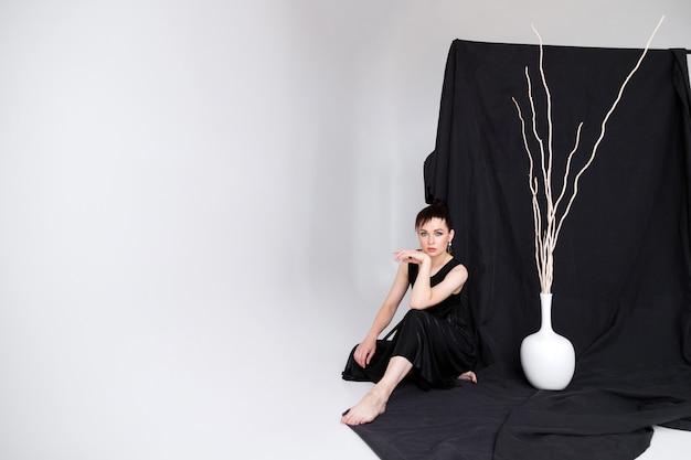 Mulher em um vestido preto minimalista sobre um fundo de tecido preto está sentada no estúdio.