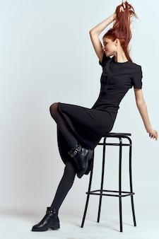 Mulher em um vestido preto, posando em uma parede de luz, modelo