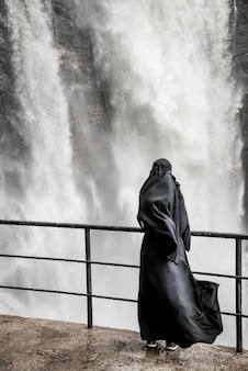 Mulher em um vestido preto tradicional está de pé perto da cachoeira. shri-lanka.