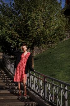 Mulher em um vestido vermelho e uma jaqueta preta masculina no parque no verão.