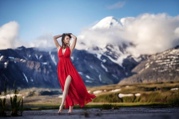 Mulher em um vestido vermelho longo posando em montanhas majestosas.