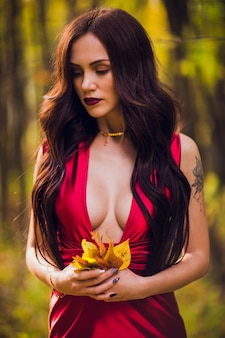Mulher em um vestido vermelho longo sozinho na floresta. imagem fabulosa e misteriosa de uma garota em uma floresta escura ao sol da tarde. pôr do sol, a princesa se perdeu.
