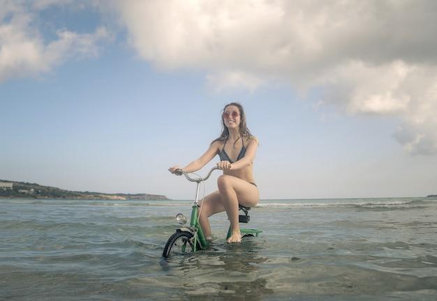 Mulher em uma bicicleta no mar