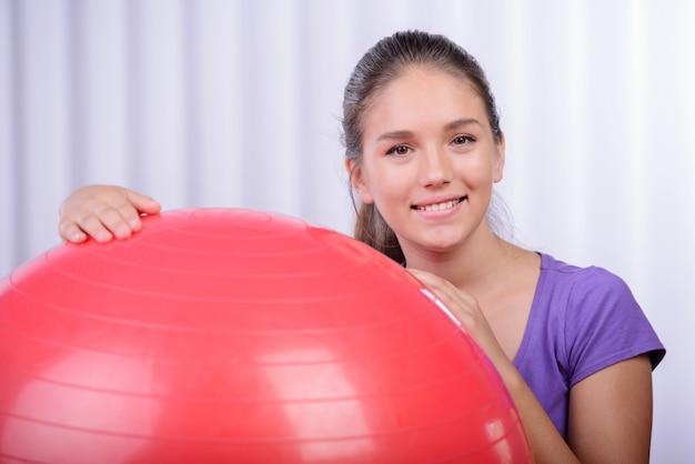 Mulher em uma bola de fitness em um sorriso de ginásio e feliz.