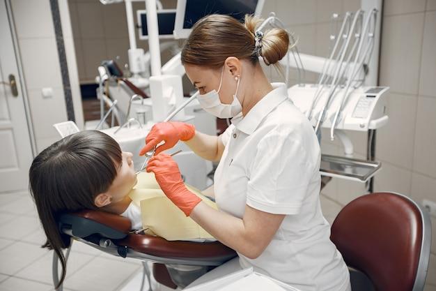 Mulher em uma cadeira de dentista. a menina é examinada por um dentista. a beleza trata os dentes