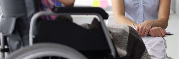 Mulher em uma cadeira de rodas em consulta com um psicólogo.