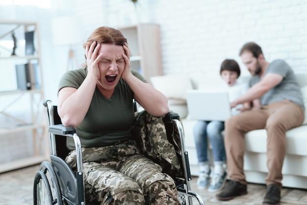 Mulher em uma cadeira de rodas está com dor ela está em uniforme militar