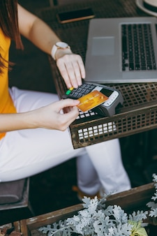 Mulher em uma cafeteria ao ar livre, sentada com um computador laptop, segura um terminal de pagamento de banco moderno sem fio para processar pagamentos com cartão de crédito