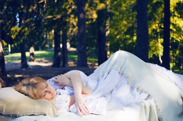 Mulher em uma cama na floresta