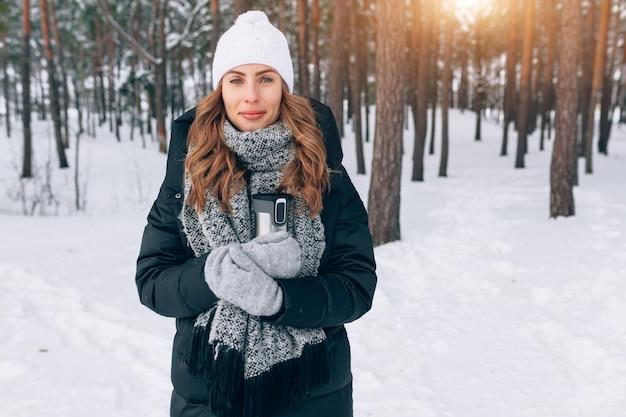 Mulher em uma caminhada na floresta de inverno beber chá de uma garrafa térmica