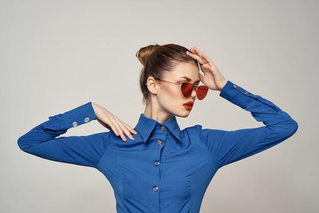 Mulher em uma camisa azul brilhante, posando de saia vermelha