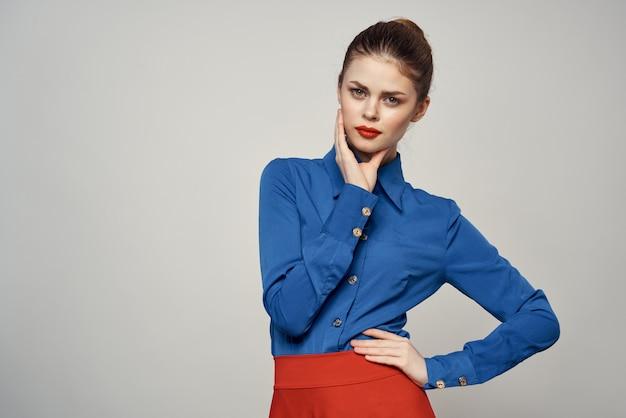 Mulher em uma camisa azul brilhante, saia vermelha, posando em um espaço colorido, imagem de negócios elegante